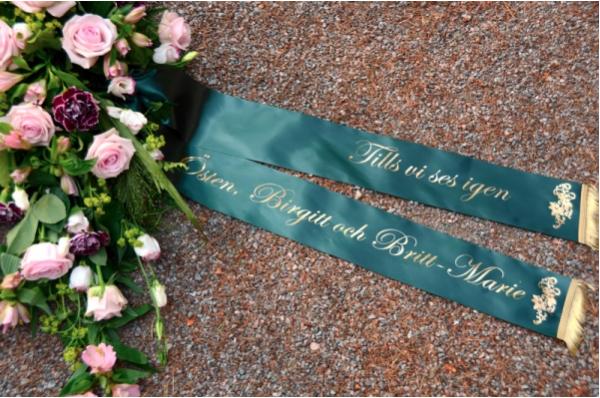 Band till begravningsblommor med text i form av namn och hälsning.