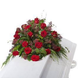 Begravningsblommor bestående av röda rosor samt grönt utfyllnad liggandes på vit kista.