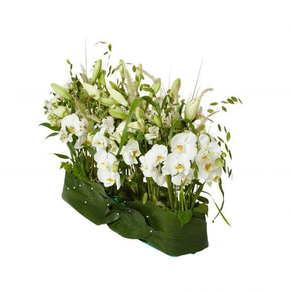 Modern sorgdekoration med begravningsblommor som står på rad med stora bland längst ner runt om blommorna. Dekorationen har ett grönt färg schema och innehåller blommor så som liljor, orkidéer samt vita strån m.m.