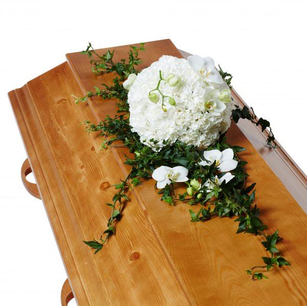 Vit dunboll som används som kistdekoration på en brun begravningskista gjord av vita orkide klockor och vackra slingrande murgröna.