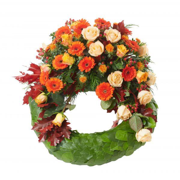 Begravningskrans gjord på blad med inspiration av hösten.Längst upp på kransen finns det blommor och ekblad i oreanga och röda toner. Kransen är i mitten av en vit bakgrund och är en begravningsblomma.