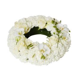 Vit,fräsch och stilren urndekoration i form av en begravningskrans. Begravningskransen är gjord av vita krysantemum med inslag av romantiska orkidéer. Dekorationen har även vita pärlor.