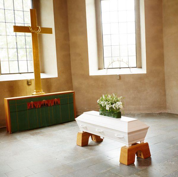 Svansjön med vit kista i kyrka