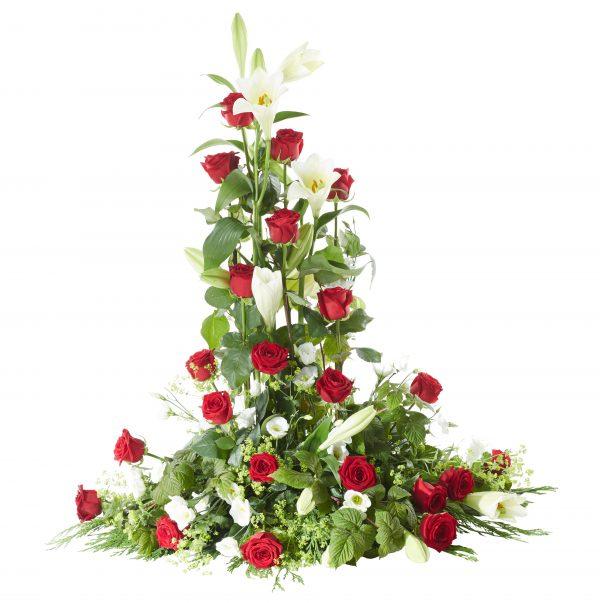 Klassisk och traditionell fristående sorgdekoration i färgerna rött och vitt med rosor,liljor och vita prärieklockor. Buketten är en begravningsblomma och är i mitten av en vit bakgrund.