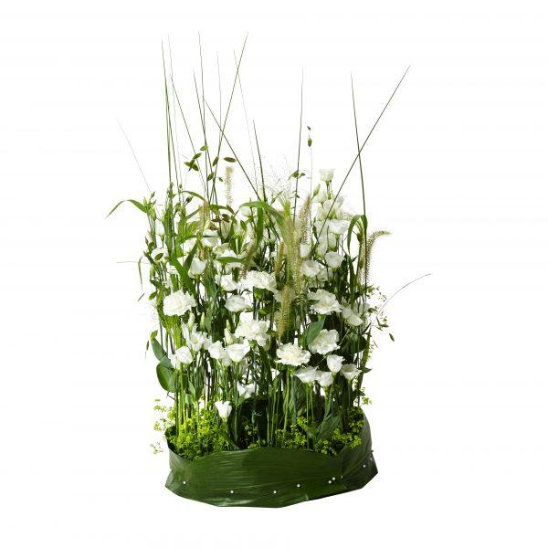 Grön sorgdekoration med fina vita nejlikor,vita alstroemeria,prärieklockor,daggkåpa,aspidistrablad och skira strån. Blommorna är begravningsblommor och ligger i en grön krans och står ståendes.