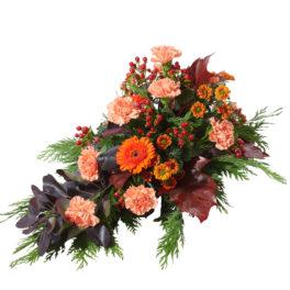 Sorgdekoration med vackra begravningsblommor så som nejlika,krysantemum,germini,hypericum och blad i höstfärger. Buketten ligger i mitten av en vit bakgrund.