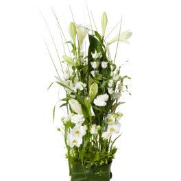 Fristående sorgdekoration med begravningsblommor i vit och grönt, bland annat med blommor som vita prärieklockor och orkidéer. Längst ner på dekorationen finns ett blad runt blommorna.
