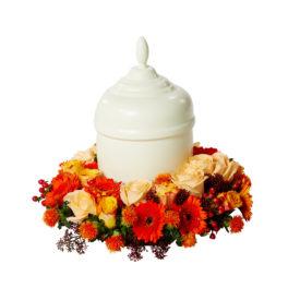 Urndekoration med begravningsblommor i varma färger som speglar en solnedgång, det vill säga i orange,gul och rött. Blommorna omfamnar en vit urn och är germini,hypericum,skimmia och tistlar.