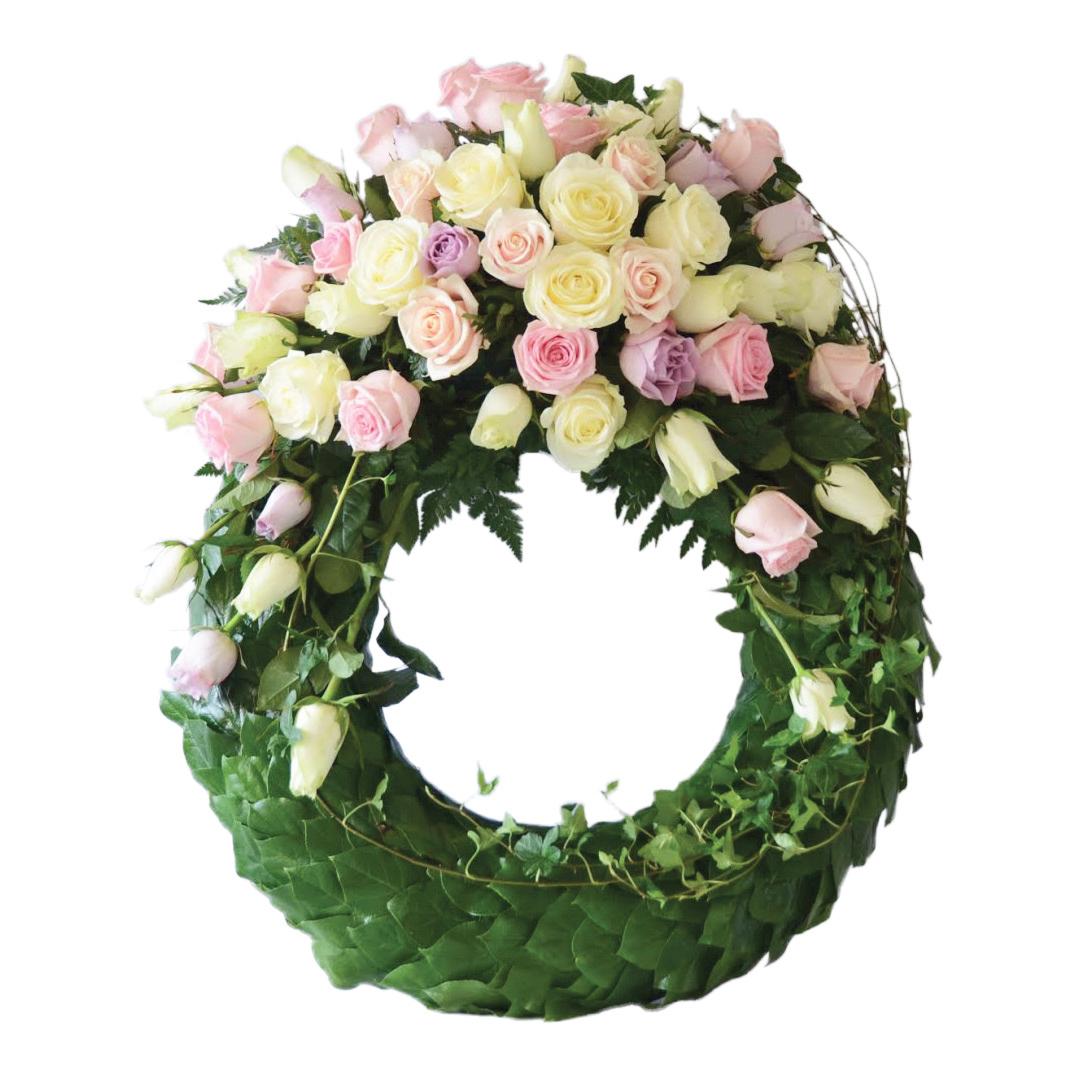Grön begravningskrans gjord på blad. Längst upp på kransen finns det rosor i romantiska pastellfärger och murgröna. Kransen är en begravningsblomma och är i mitten av en vit bakgrund.