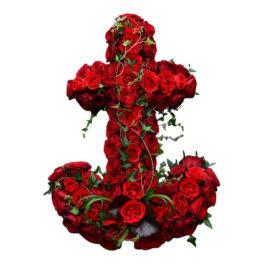 Begravningsblomma med röda rosor som formar ett ankare i rött med murgröna som slingrar sig vackert runtom ankaret. Ankaret är ett personligt arrangemang och är i mitten av en vit bakgrund.