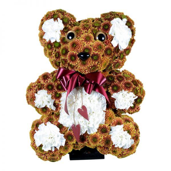 Begravningsblomma i form av en teddy björn gjord av krysantemum. Nallebjörnen har en rosett runt halsen och är brun med vita detaljer. Dekorationen är i mitten av en vit bakgrund och är ett personligt arrangemang.