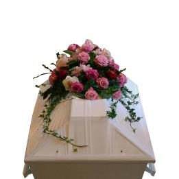 Begravningsblommor bestående av ljus rosa färger samt murgröna på vit begravningskista.