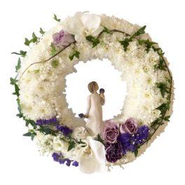 Vit begravningskrans med krysantemum.Runt kransen finns det kvistar med blad bundna.I mitten är en willow-figur.Brevid figuren till vänster finns det lila blommor. Kransen är i mitten av en vit bakgrund och är en begravningsblomma.