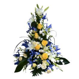 Sorgdekoration med traditionella begravningsblommor som har inspiration av Sverige. Buketten består av vita liljor,gula rosor,blå iris och har gröna blad. Buketten är i mitten av en vit bakgrund.