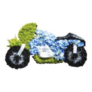 Begravningsblomma i form av en motorcykeln. Dekorationen har svarta däck gjord av svarta blommor och cykeln är blå,vit och grön. Dekorationen är ett personligt arrangemang