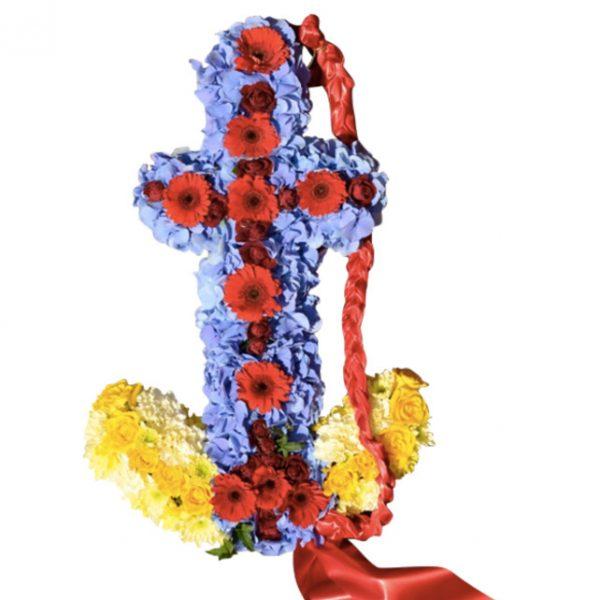 Begravningsblomma i djurgårdens färger, det vill säga blå,gul och röd. Dekorationen är gjord av blommor och formar ett ankare. Ankaret är ett personligt arrangemang.