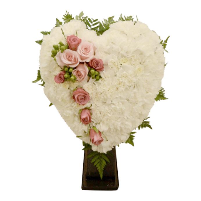 Begravningsblomma fylld med vita nejlikor som utformar ett stort vit hjärta. Hjärtat har även en dekoration med ljusa rosor samt blad som sticker ut ur bakom hjärtat.