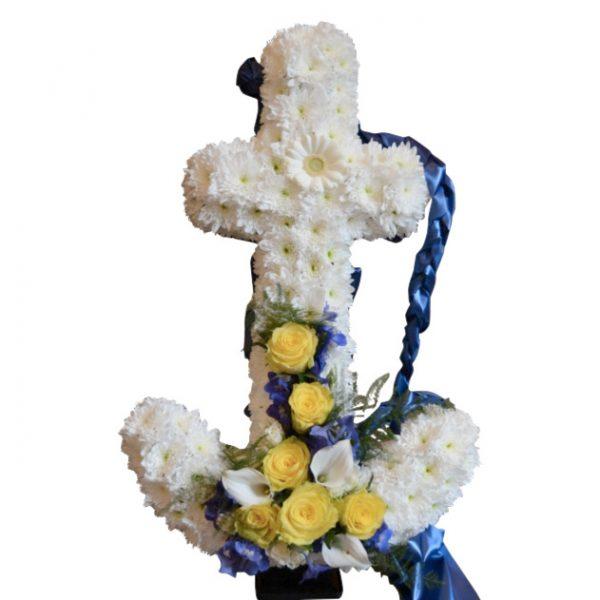 Begravningsblomma som utformar ett vitt ankare med vita och blå detaljer. Gula och vita blommor är längst ner i mitten på ankaret, och ett blått band hänger ner bakifrån ankaret.Ankaret är ett personligt arrangemang.