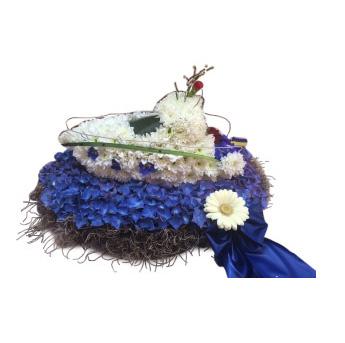 Begravningsblomma som utformar en båt som åker över havet. Dekorationen är gjord av blommor i färgerna blå och vitt. Där den blåa färgen motsvarar havet och de vita blommorna båten.Båten är ett personligt arrangemang.