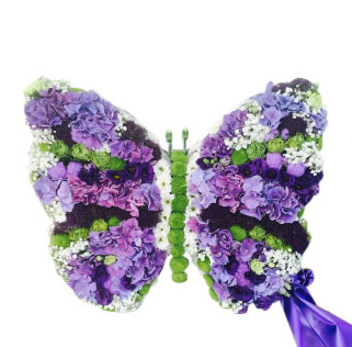Begravningsblomma som utformas till en fjäril i lila nyanser och gröna detaljer. Fjärilen har även ett lila band som hänger ner på den vänstra sidan av vingen.Fjärilen är ett personligt arrangemang.
