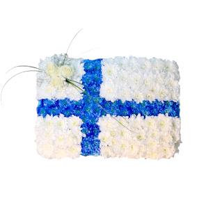 Begravningsblomma gjord av blommor i vit och blå som formar den finska flaggan. Längst upp mot höger på flaggan finns det 3 rosor.Dekorationen är ett personligt arrangemang.