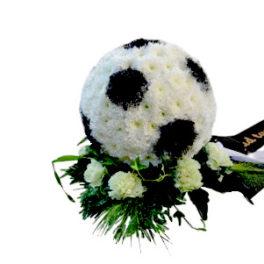 Begravningsblomma i form av en svart vit klassisk fotboll.Fotbollen ligger på gröna blad och vita blommor och är ett personligt arrangemang.