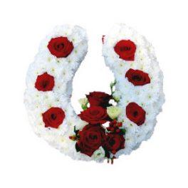 Begravningsblomma som utformar en hästsko. Dekorationen är gjord av vita blommor och har röda ros detaljer. Dekorationen är ett personligt arrangemang.
