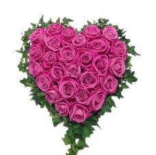 Liten sorgdekoration med stora rosa rosor och blad längst kanten som format ett hjärta. Hjärtat är ett rosa ros hjärta i mitten av en vit bakgrund och är en begravningsblomma.