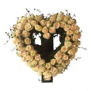 Flera champagne färgade rosor som utformar en begravningsblomma i form av ett hjärta med gröna talea som vackert kompletterar rosorna. Dekorationen är i mitten av en vit bakgrund.