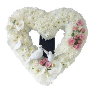 Begravningsblomma som består av ett stort öppet orkidéerhjärta fylld med vita krysantemum, ett par orkidéerklockor,rosa kvistrosor och två duvor längst ner vid hjärtats öppning.