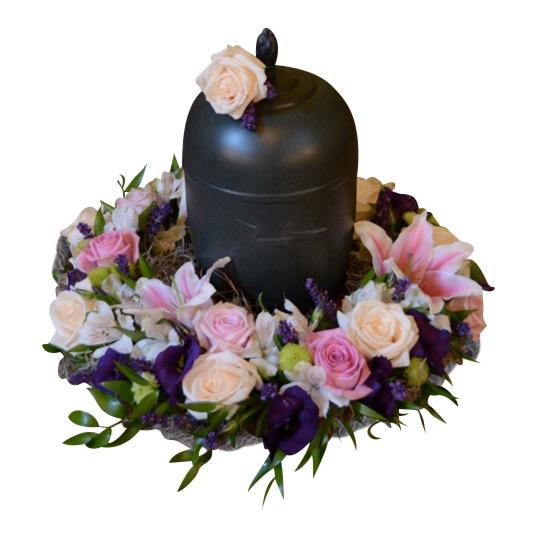 Urndekoration med begravningsblommor. Blommorna är champagnefärgade och rosa rosor, rosa liljor och blå iris. Dekorationen omslutar en svart urn med en champagneros på ovansidan av urnen.