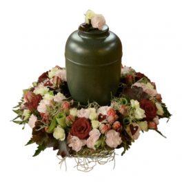 Urndekoration gjord på begravningsblommor i rosa och röda toner,bland annat rosor.Dekorationen har även små hjärtan.I mitten av kransen är en mörkgrön urn med rosor på ovansidan.
