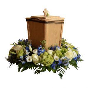 Brun trä urn med kristet kors på ovansidan. Urnen är i mitten av en urndekoration med flertal begravningsblommor som formar en urnkrans i färgerna svalkande blå,vit och svaga gröna toner.