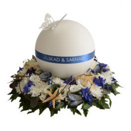 Vit rund urn.På ovansidan av urnen är en vit fjäril. I mitten är en blå rand med texten ''Älskad och saknad'' Under urnen är en urndekoration gjord på begravningsblommor med blå färg och havs schema.