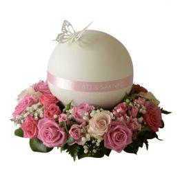 Urndekoration med begravningsblommor i rosor i olika rosa toner samt med vita rosor och blad. I mitten av dekorationen är en rund urn i i vitt och rosa och med en vit fjäril på ovansidan.
