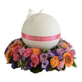 Urndekoration med färgstarka begravningsblommor i cerise,lila,orange och rosa.På begravningsblommorna är en rund urndekoration i vitt och rosa med en fjäril på ovansidan.