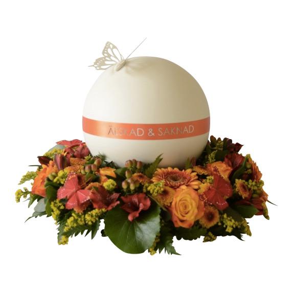Rund vit urn med orangea detaljer. På ovansidan av urnen är en vit fjäril. Urnen ligger i mitten på en urndekoration med begravningsblommor i orange.rött och med fjärilar.