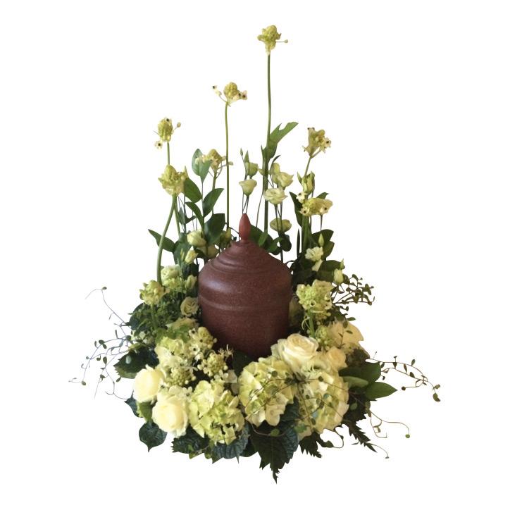 Liten brun urn som har vita och lime färgade begravningsblommor, samt grönt omkring sig. Urnen är i mitten av urndekorationen och blommorna omfamnar vackert urnen.