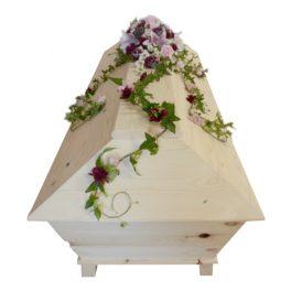 Begravningsblommor på en ljus begravningskista gjord av träd, blommorna är rosa och cerise /lila, rosor,kryss samt med murgröna.