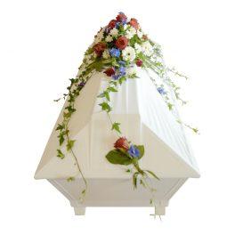 Begravningsblommor används som kistdekoration på vit kista, blommorna är i färgerna vitt,blått och röd. Blommorna är rosor gerbera,delfinium mm...