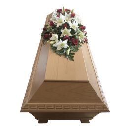 Klassisk samt traditionell begravningsblommor liggandes på ljusbrun kista, i röda rosor, vita liljor och brudslöja.