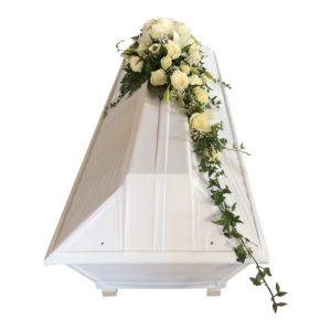 Begravningsblommor med vita rosor, brudslöja samt murgröna liggandes på en vit kista som kistdekoration.