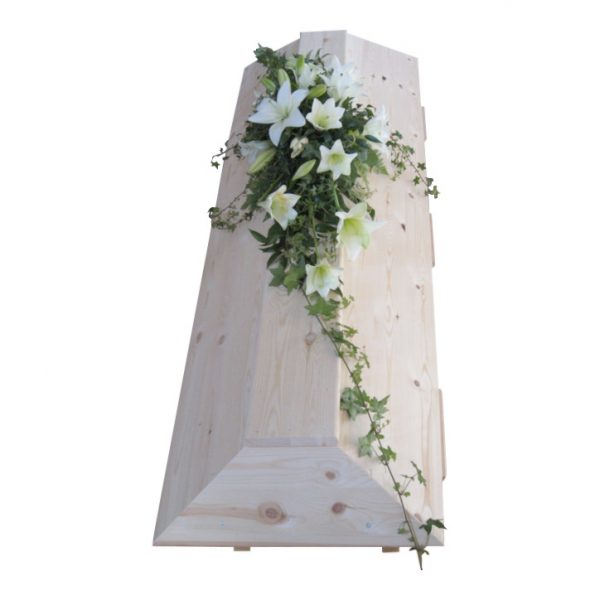Kistdekoration med begravningsblommor som består av vita liljor och murgröna som ligger på en ljus begravningskista.