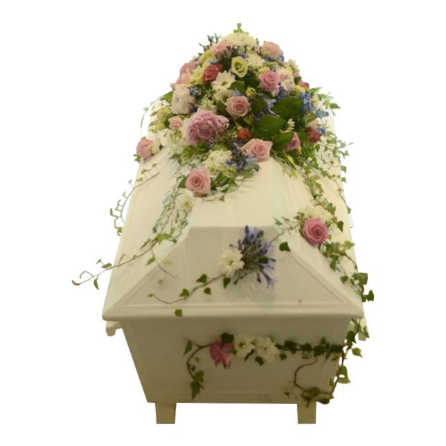 Begravningsblommor som innehåller blandade blommor i färgerna ljus blå. rosa samt vit. Kistdekorationen slingrar sig runt den vita kistan. Färgerna av blommorna skapar en sommar känsla.