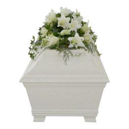 Begravningsblommor med vita stora liljor liggandes på vit begravningskista.