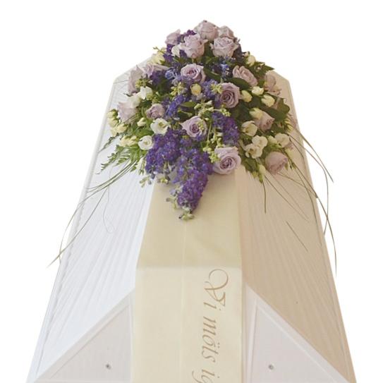 Begravningsblommor med lila färgschema på vit begravningskista med text på, blomsorten är ocean song rosor, och prärieklocka.