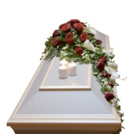 Begravningskista med begravningsblommor innehåller röda rosor och vita anturium. lejongap samt 3 stora ljus.