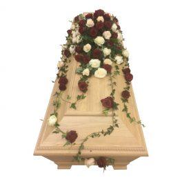 Begravningsblommor i färgerna och sorterna champagne,röda och vita rosor samt murgröna. Blommorna ligger på en begravningskista i ljus brun färg.
