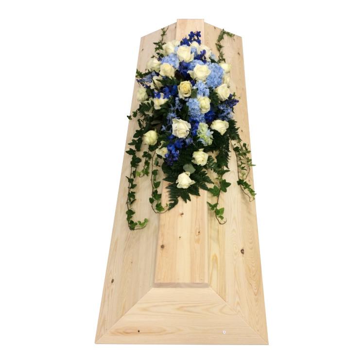 Begravningsblommor som används som kistdekoration på begravningskista gjord av träd. Blommorna är vita rosor,blå hortensia,delfinium och lite murgröna. Blommorna ger en havskänsla.