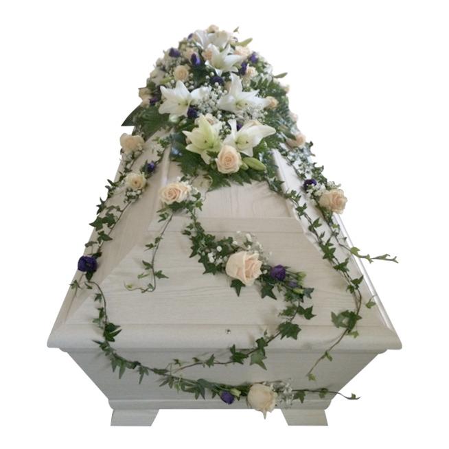 Begravningsblommor på vit begravningskista,blommorna består av champagnerosor, vita liljor, lila prärieklocka, brudslöja samt murgröna som hänger ner över kistan som en kistdekoration.
